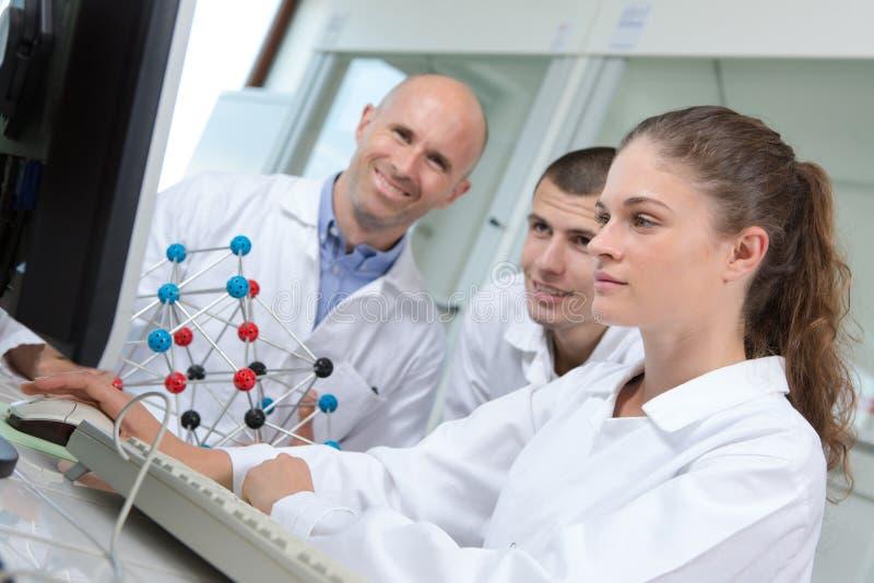 有脱氧核糖核酸模型的年轻科学家在实验室 免版税库存照片