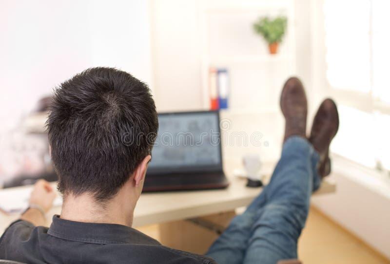 有腿的人在书桌上在办公室 免版税库存照片