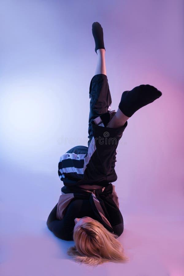有腿的可爱的妇女在空气和体育田径服显示他的在五颜六色的背景的体操技能 免版税库存照片