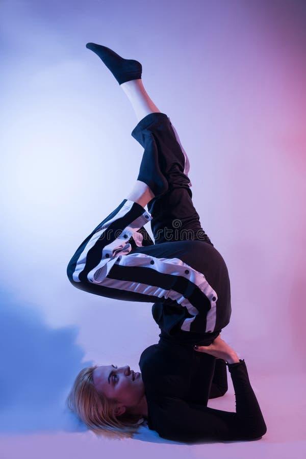 有腿的少女在空气和体育田径服显示他的在五颜六色的背景的体操技能 免版税图库摄影