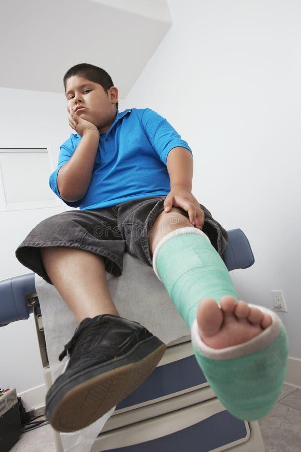 有腿的男孩在石膏模型 免版税图库摄影
