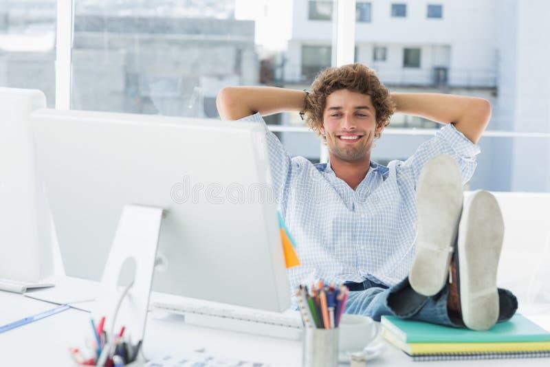 有腿的轻松的偶然人在书桌上在明亮的办公室 免版税图库摄影