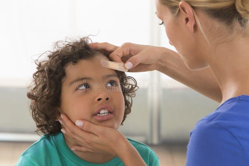 有膏药的母亲儿童的创伤 免版税库存照片