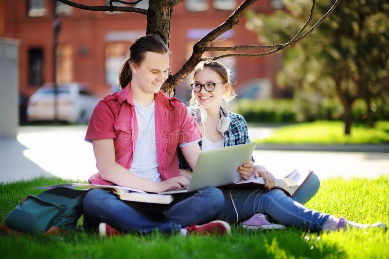 有膝上型计算机、书和笔记的年轻愉快的学生户外 库存照片