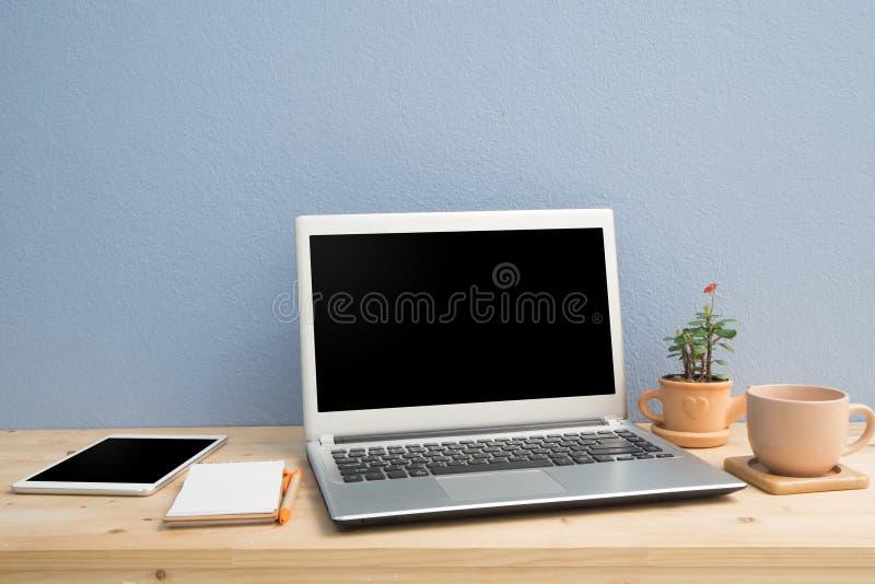 有膝上型计算机、便条纸,大戟属milii花的办公桌在赤土陶器花盆和黑屏片剂 免版税库存图片