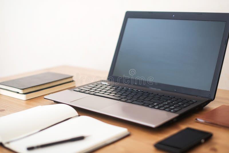 有膝上型计算机、巧妙的电话和笔记本的办公室工作场所在木桌上 免版税库存图片