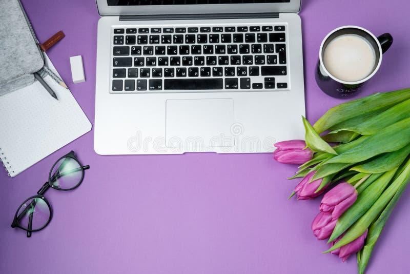 有膝上型计算机、早晨咖啡和郁金香的妇女桌面在紫罗兰色b 库存照片
