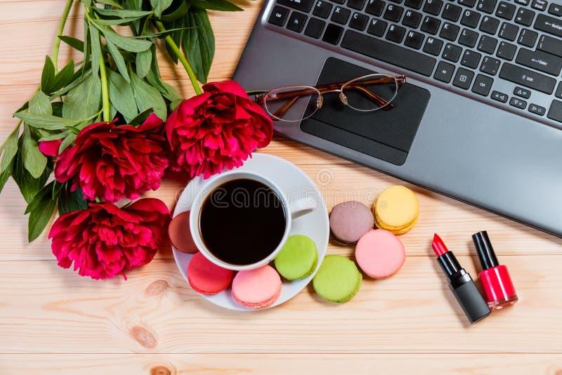 有膝上型计算机、牡丹花、唇膏和咖啡的书桌 免版税库存图片