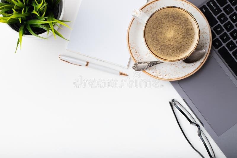 有膝上型计算机、眼睛玻璃、笔记薄、笔和一杯咖啡的书桌在一张白色桌上的 与拷贝空间的顶视图 平的位置 轻的backgr 免版税图库摄影