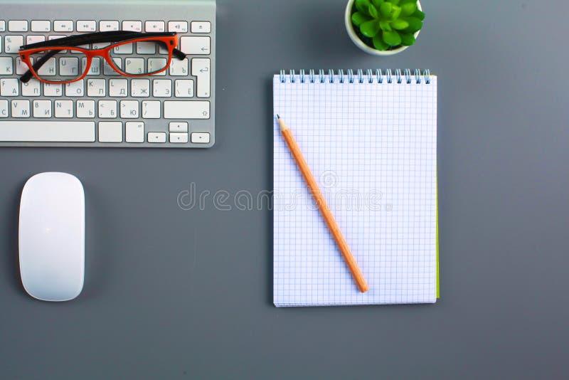 有膝上型计算机、笔和笔记本的办公桌 顶视图 图库摄影
