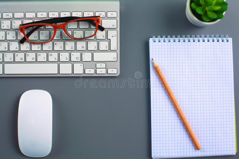 有膝上型计算机、笔和笔记本的办公桌 顶视图 库存图片