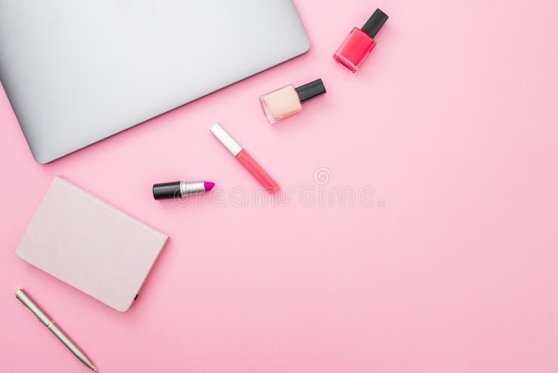 有膝上型计算机、笔记本和化妆用品的女性书桌在淡色背景 平的位置生活方式概念 图库摄影