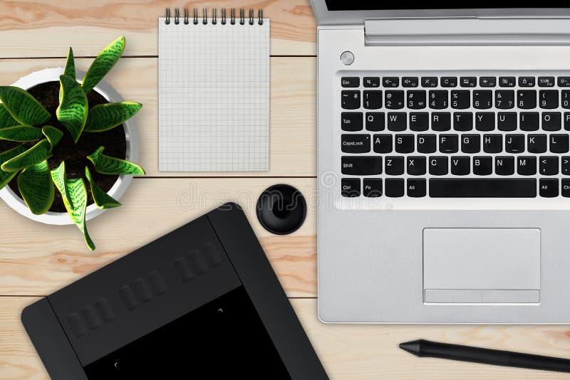 有膝上型计算机、笔记薄与空白纸,罐花,铁笔和片剂的木书桌修饰的 专业reto工作区  免版税图库摄影