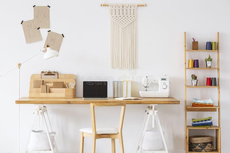 有膝上型计算机、缝纫机、组织者和花边的o木书桌在架子旁边的墙壁 空的屏幕,安置您 免版税库存图片