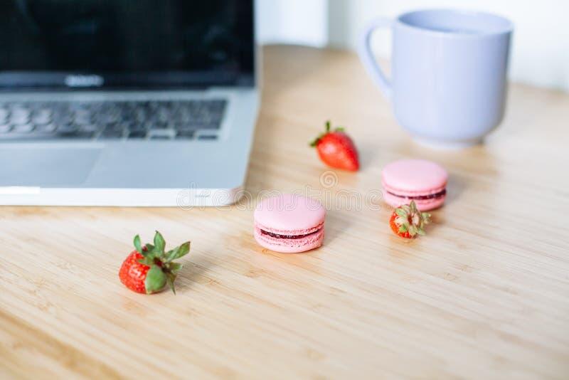 有膝上型计算机、蛋白杏仁饼干、草莓和茶的工作场所 库存照片