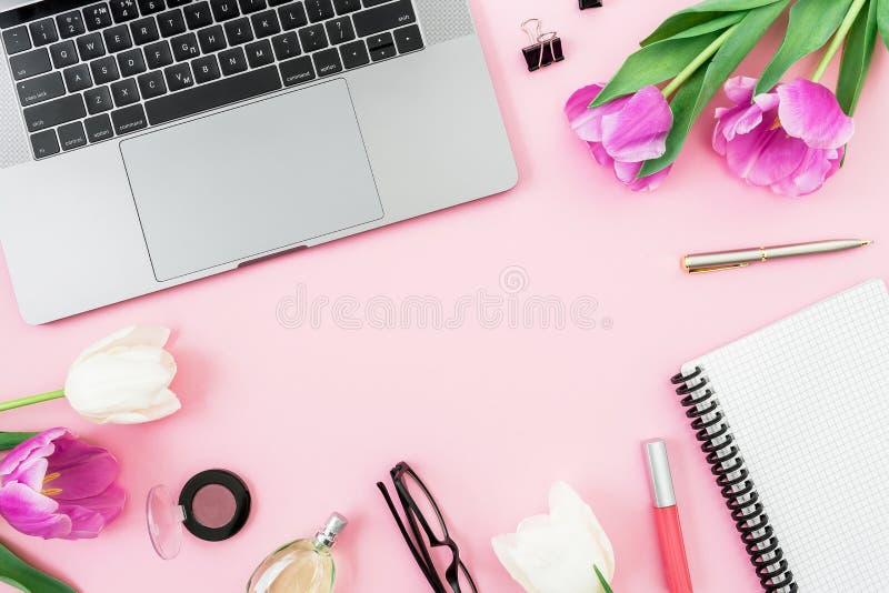 有膝上型计算机、郁金香花、化妆用品、玻璃和笔的女性办公桌在桃红色背景 平的位置 顶视图 与c的概念 库存照片