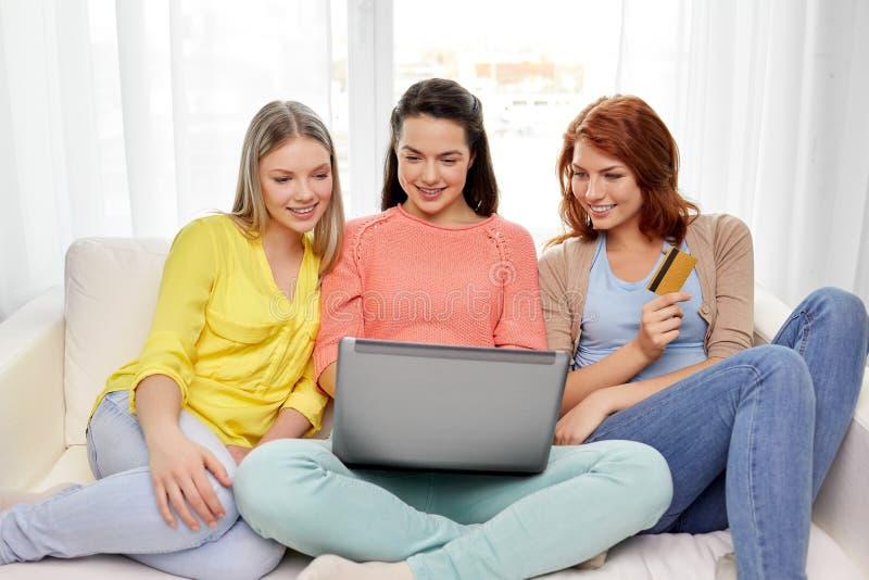 有膝上型计算机和信用卡的十几岁的女孩 免版税库存图片