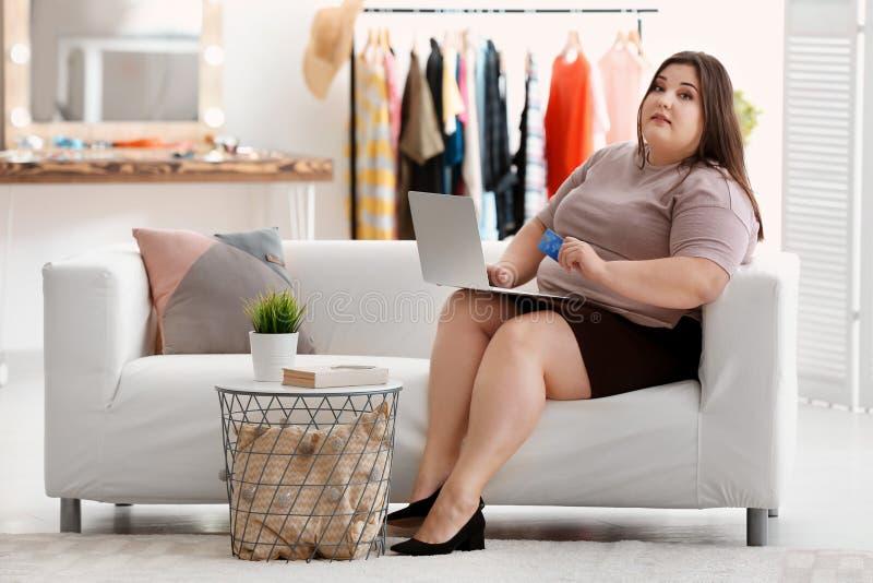 有膝上型计算机和信用卡的美丽的超重妇女 库存图片
