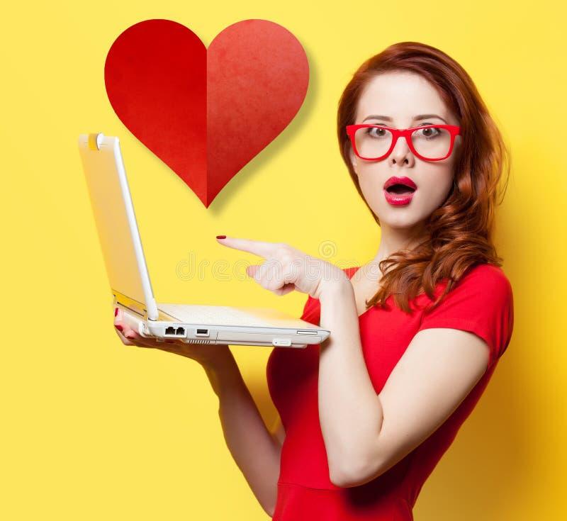 有膝上型计算机和心脏的惊奇的红头发人女孩 免版税库存图片