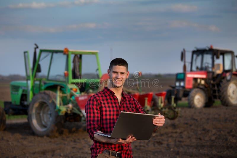 有膝上型计算机和拖拉机的农夫 库存图片