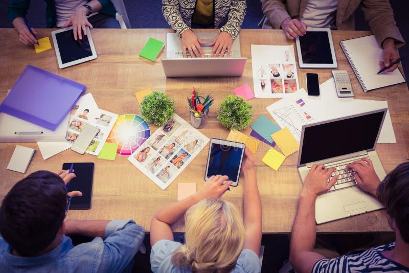 有膝上型计算机和数字式片剂办公室的创造性的同事 免版税库存照片