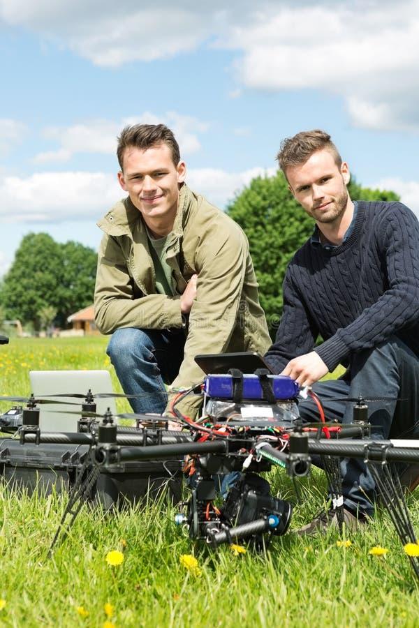 有膝上型计算机和数字式片剂的技术员乘UAV 库存图片