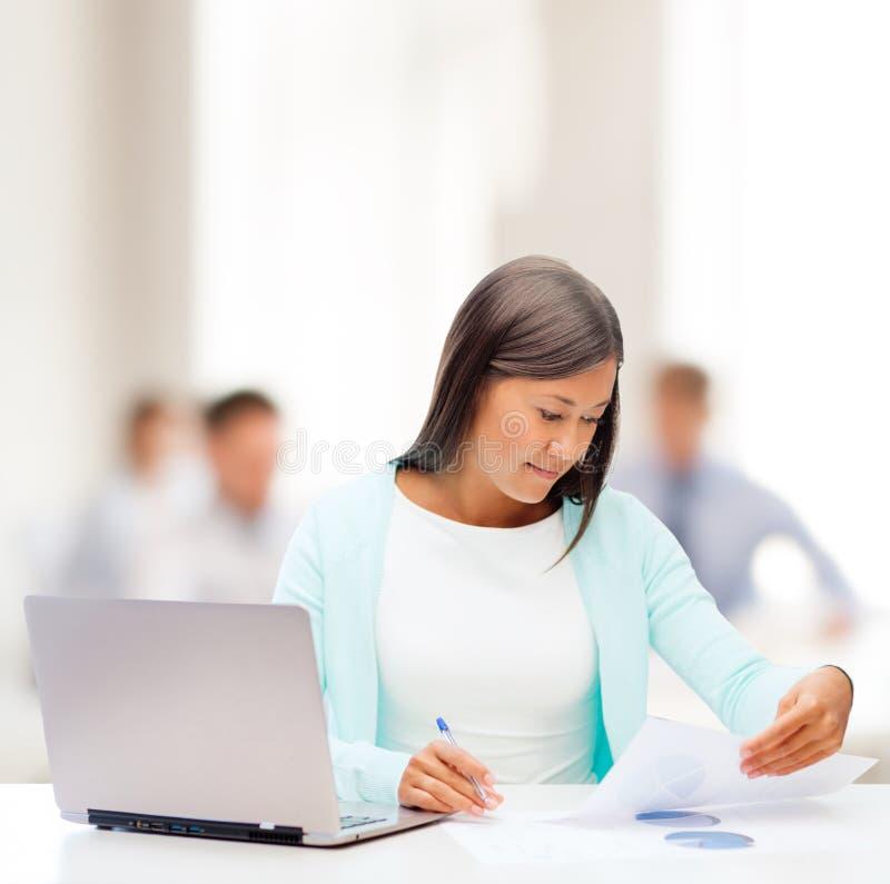 有膝上型计算机和文件的亚裔女实业家 免版税库存图片