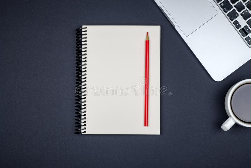 有膝上型计算机和空白的笔记薄的最小的工作场所 免版税库存照片