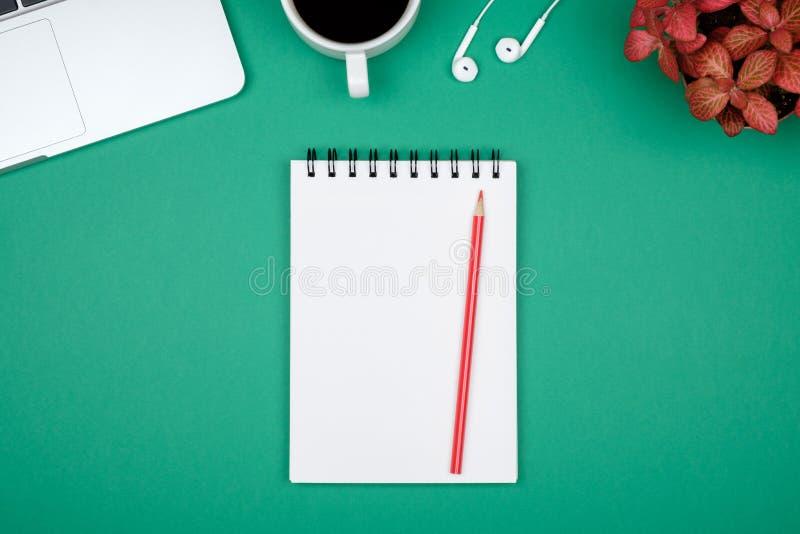 有膝上型计算机和空白的笔记薄的最小的工作场所 库存照片