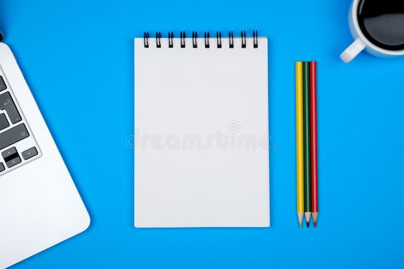 有膝上型计算机和空白的笔记薄的最小的工作场所 免版税库存图片