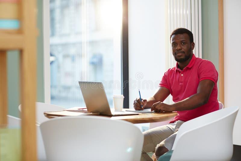 有膝上型计算机和笔记薄的偶然黑人 免版税库存图片