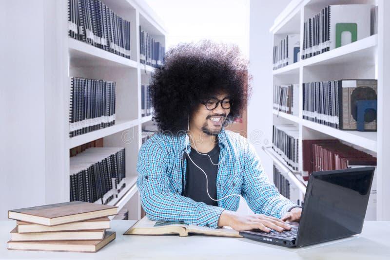 有膝上型计算机和耳机的卷曲的学生在图书馆里 免版税库存图片