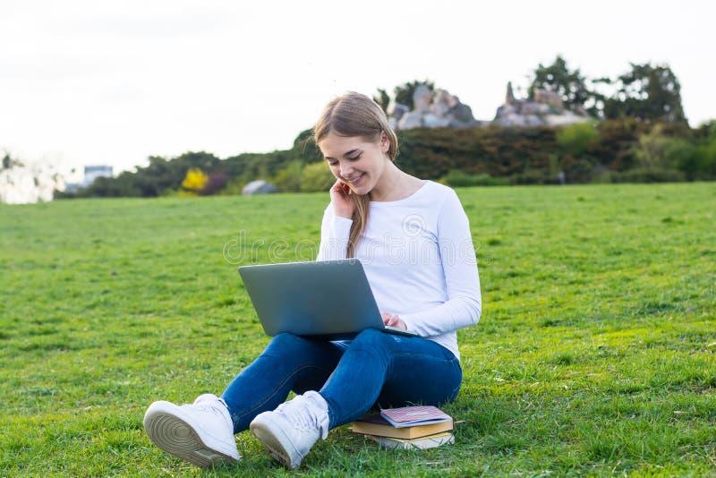 有膝上型计算机坐的和微笑的o的年轻美丽的女孩学生 库存图片