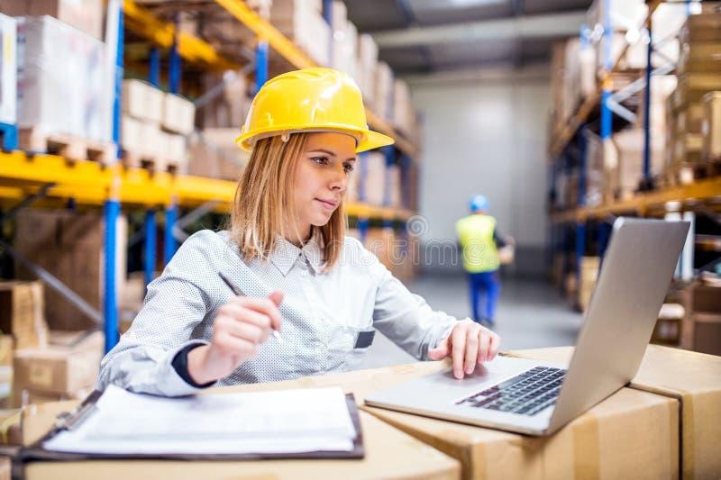 有膝上型计算机工作的年轻仓库工作者 库存图片