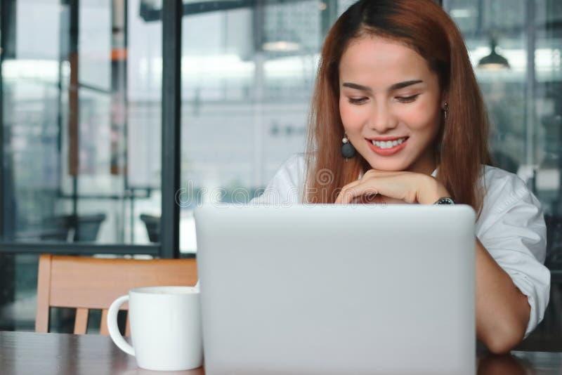 有膝上型计算机工作的微笑的年轻亚裔女商人在现代办公室 免版税库存照片