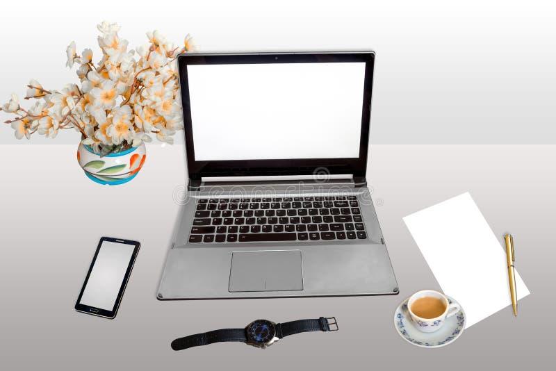 有膝上型计算机巧妙的电话手表白色白纸的工作地点和笔用在轻的梯度隔绝的早晨茶 图库摄影