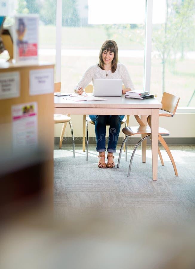 有膝上型计算机文字笔记的学生在图书馆里 库存图片
