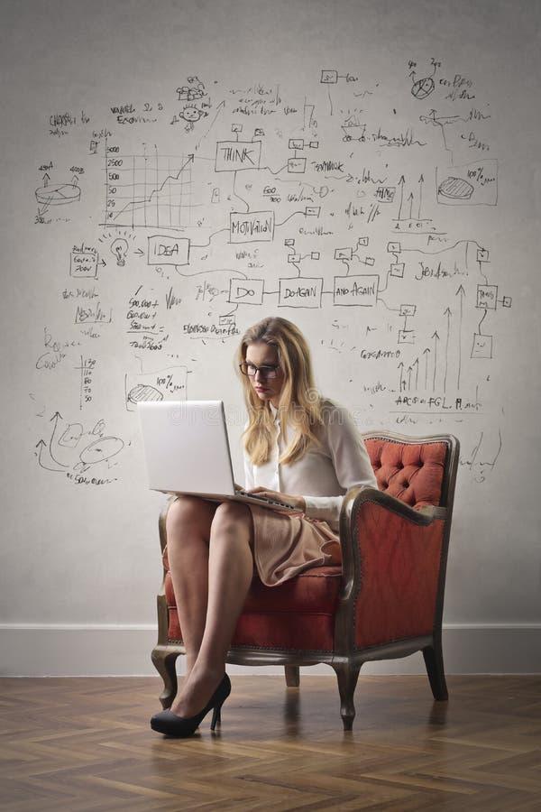 有膝上型计算机的一个女孩坐扶手椅子 库存照片