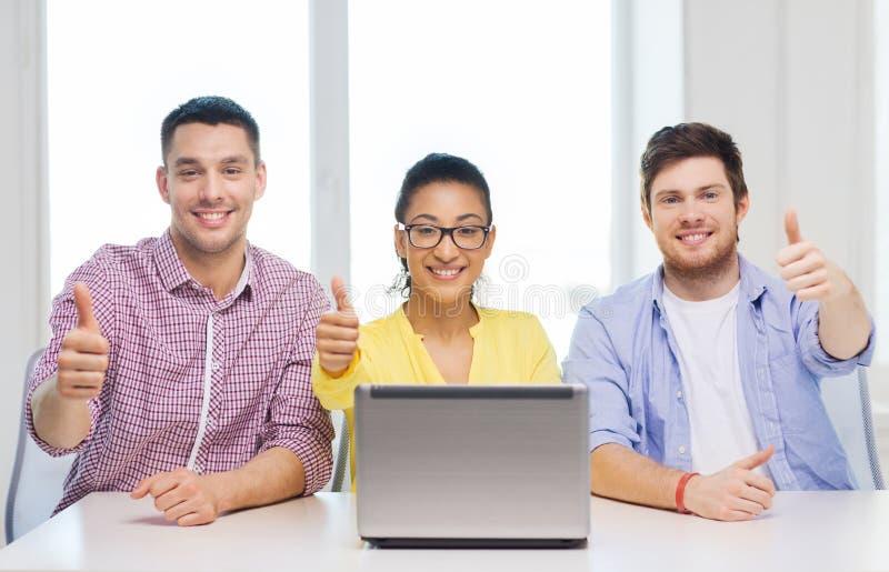 有膝上型计算机的三个微笑的同事在办公室 库存照片