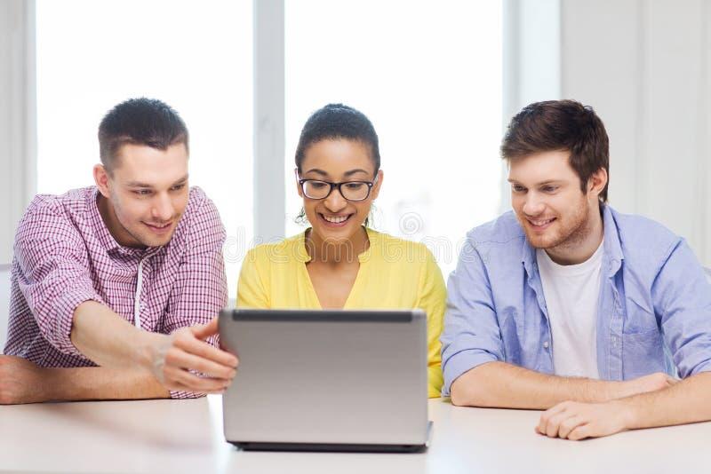 有膝上型计算机的三个微笑的同事在办公室 免版税库存照片