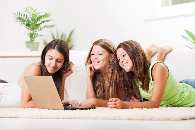 有膝上型计算机的三个快乐的朋友 免版税库存照片