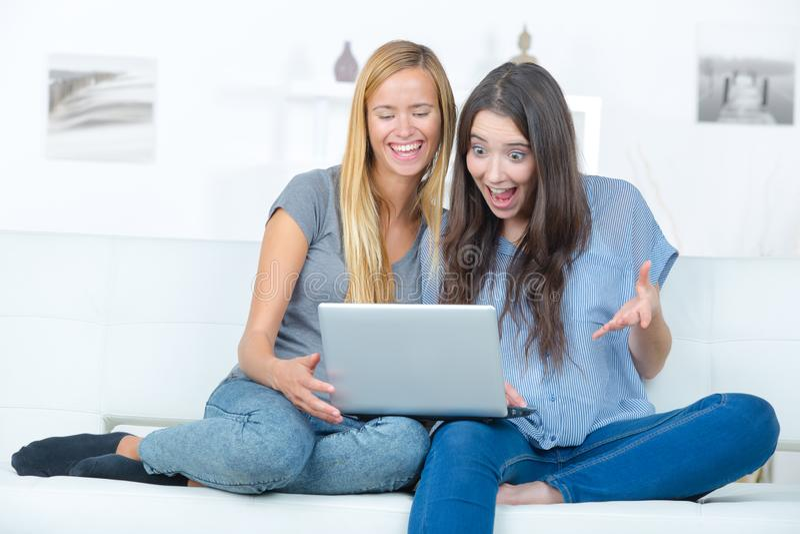 有膝上型计算机的两个愉快的年轻朋友在家 免版税图库摄影