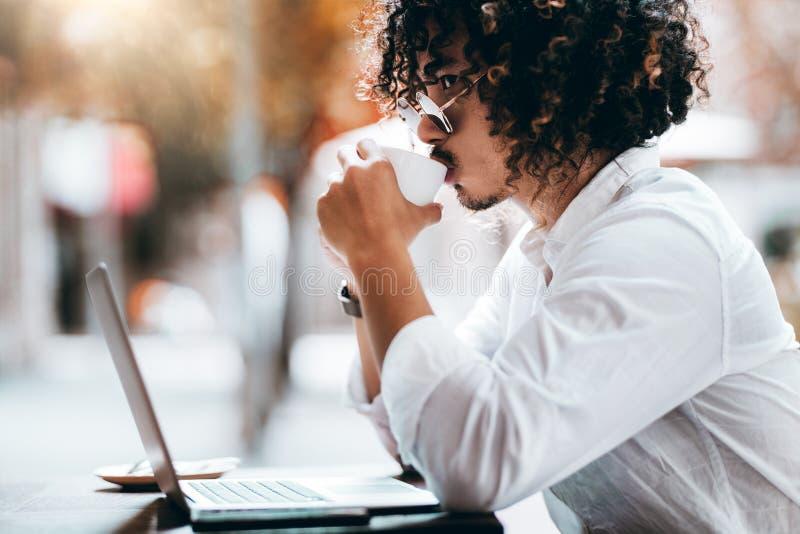 有膝上型计算机的亚裔人在街道咖啡馆饮用的咖啡 免版税图库摄影