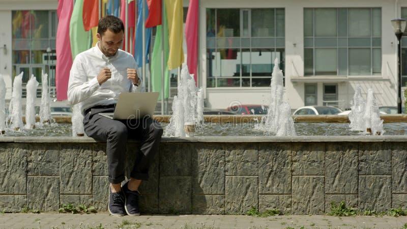 有膝上型计算机的人坐在喷泉附近和满意对他的结果工作 免版税库存图片