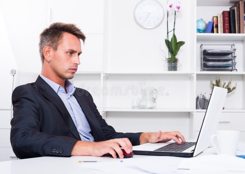 有膝上型计算机的体贴的人在办公室 库存图片