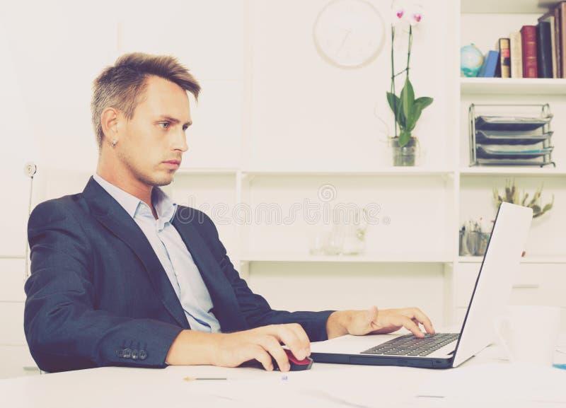 有膝上型计算机的体贴的人在办公室 图库摄影