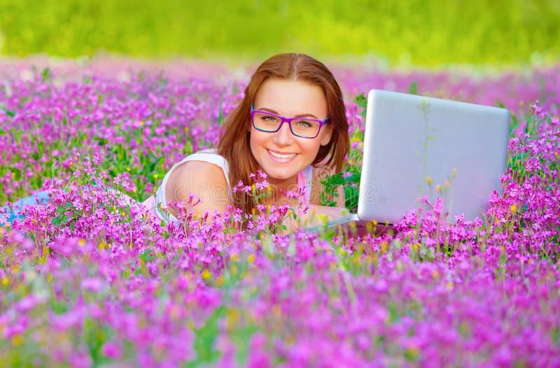 有膝上型计算机的俏丽的妇女在花卉领域 免版税库存图片
