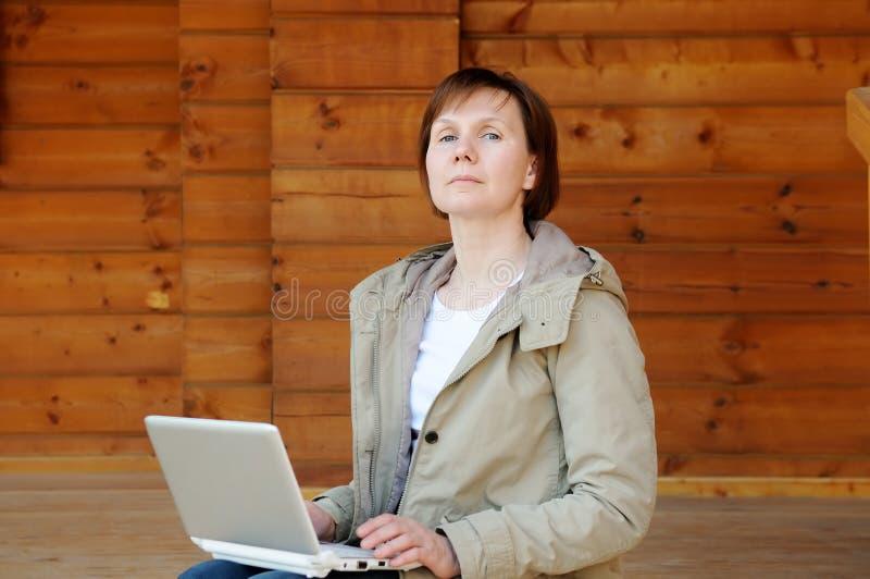 有膝上型计算机的傲慢的妇女 免版税库存照片