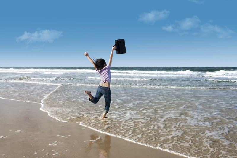 有膝上型计算机的兴奋妇女在海滩 免版税库存照片