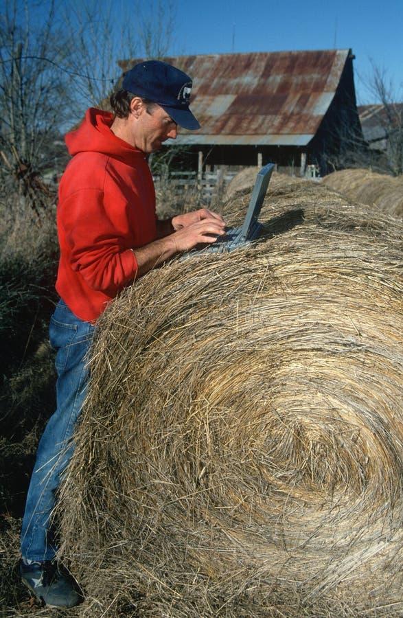有膝上型计算机的农夫在干草捆 库存图片